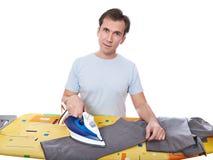 Счастливый человек утюжа его серые изолированные брюки стоковое изображение