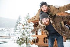 Счастливый человек piggibacking его подруга и смеясь над в зиме стоковое изображение rf