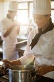 Счастливый шеф-повар варя на плите Стоковые Фото