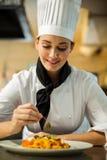 Счастливый шеф-повар гарнируя блюдо макаронных изделий с оливкой Стоковое Изображение RF