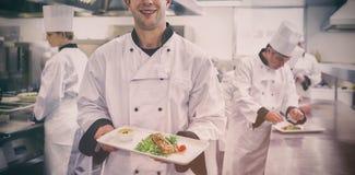 Счастливый шеф-повар держа salmon блюдо Стоковая Фотография