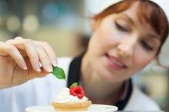 Счастливый шеф-повар кладя лист мяты на меньший торт Стоковая Фотография