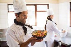 Счастливый шеф-повар представляя его еду Стоковое фото RF