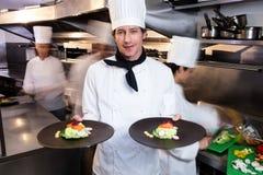 Счастливый шеф-повар представляя его плиты еды Стоковые Изображения RF