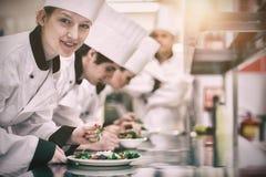 Счастливый шеф-повар смотря вверх от подготавливать салат Стоковая Фотография