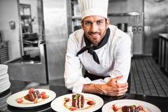 Счастливый шеф-повар смотря камеру за счетчиком десертов Стоковая Фотография RF