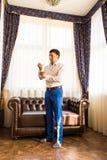 Счастливый шикарный красивый groom получая готовое одетый в утре на предпосылке комнаты Стоковое Фото
