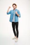 Счастливый excited молодой человек стоя и празднуя успех Стоковые Изображения RF