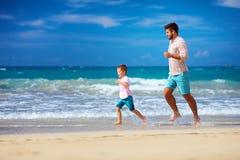 Счастливый excited отец и сын бежать на лете приставают к берегу, наслаждаются жизнь Стоковое фото RF
