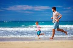 Счастливый excited отец и сын бежать на лете приставают к берегу, наслаждаются жизнь Стоковые Фотографии RF