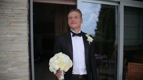 Счастливый groom ждет его невесту Молодой человек ждать его невесту в внешней свадьбе видеоматериал