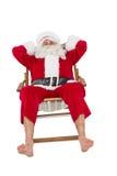 Счастливый santa ослабляя на deckchair Стоковые Изображения