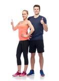 Счастливый sportive человек и женщина показывая большие пальцы руки вверх стоковое изображение rf