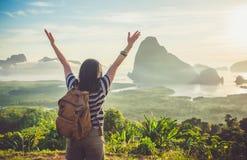 Счастливым молодым рука женщины путешественника поднятая backpacker до неба наслаждается Стоковое Изображение RF