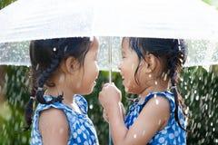 2 счастливых азиатских маленькой девочки с зонтиком Стоковая Фотография