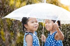 2 счастливых азиатских маленькой девочки с зонтиком Стоковое Изображение RF