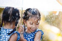 2 счастливых азиатских маленькой девочки с зонтиком Стоковое фото RF
