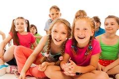 2 счастливых беседуя девушки сидят в группе в составе друзья Стоковое фото RF