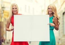 2 счастливых белокурых женщины с пустой белой доской Стоковые Изображения