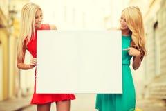 2 счастливых белокурых женщины с пустой белой доской Стоковое Изображение