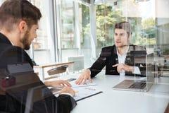 2 счастливых бизнесмена обсуждая бизнес-план на встрече в офисе Стоковые Изображения