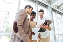 3 счастливых бизнесмены смотря через документы совместно в офисе Стоковые Фотографии RF