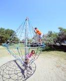 2 счастливых брать играя на спортивной площадке на carousel с Стоковое фото RF