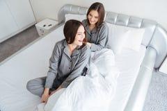 2 счастливых близнеца сестер сидя на кровати и смеяться над Стоковая Фотография RF