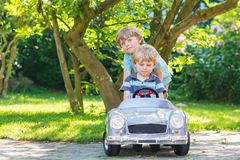 2 счастливых двойных мальчика играя с автомобилем игрушки Стоковое фото RF