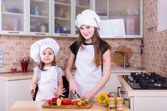 2 счастливых девушки варя на кухне Стоковая Фотография RF