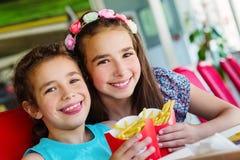 2 счастливых девушки в ресторане фаст-фуда Стоковое Изображение RF