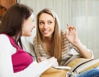 2 счастливых девушки говоря на софе Стоковые Изображения RF