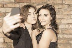 2 счастливых девушки делают selfie на мобильном телефоне Стоковые Изображения RF