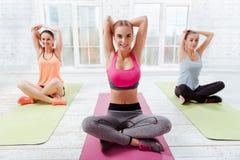 3 счастливых девушки делая йогу Стоковые Изображения