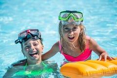 2 счастливых девушки играя в бассейне на солнечный день Милые маленькие девочки наслаждаясь каникулами праздника Стоковая Фотография