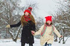 2 счастливых девушки играя на снеге в зимнем дне внешнем Стоковое фото RF
