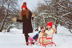 2 счастливых девушки играя на снеге в зимнем дне внешнем Стоковое Фото