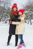 2 счастливых девушки играя на снеге в зимнем дне внешнем Стоковая Фотография
