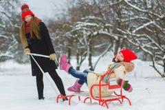 2 счастливых девушки играя на снеге в зимнем дне внешнем Стоковые Изображения