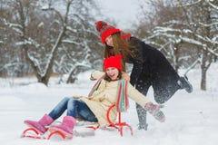 2 счастливых девушки играя на снеге в зимнем дне внешнем Стоковое Изображение