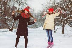 2 счастливых девушки играя на снеге в зимнем дне внешнем Стоковые Фотографии RF