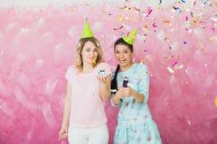 2 счастливых девушки празднуют вечеринку по случаю дня рождения с confetti a пирожного Стоковое Фото