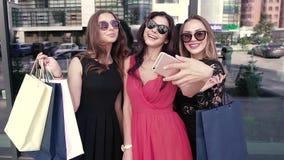 3 счастливых девушки принимая изображения и ходить по магазинам видеоматериал