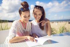 2 счастливых девушки сидя на таблице кафа на меню чтения пляжа Стоковая Фотография