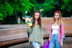 2 счастливых девушки с скейтбордом outdoors в свете захода солнца Активные sporty женщины имея потеху совместно в парке конька Стоковые Фотографии RF