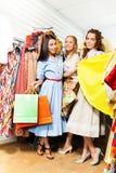 3 счастливых девушки с хозяйственными сумками в магазине Стоковые Изображения RF