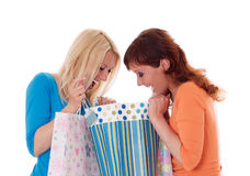2 счастливых девушки с хозяйственными сумками. Стоковая Фотография