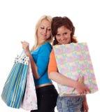 2 счастливых девушки с хозяйственными сумками. Стоковое Фото