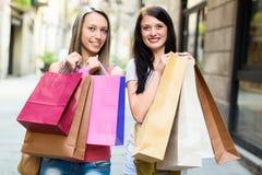2 счастливых девушки с хозяйственными сумками Стоковое фото RF