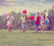 4 счастливых дет бежать на зеленой лужайке Стоковые Фотографии RF